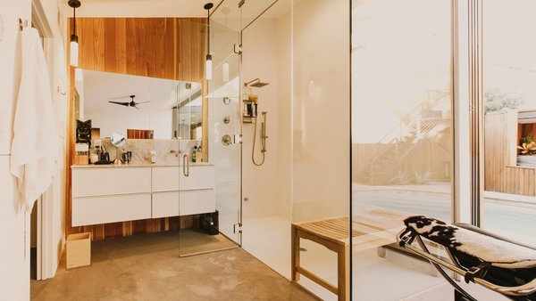 Modern home with bath room, concrete floor, undermount sink, pendant lighting, porcelain tile wall, enclosed shower, marble counter, ceiling lighting, and two piece toilet. Master bathroom featuring a steam shower Photo 2 of Curves House
