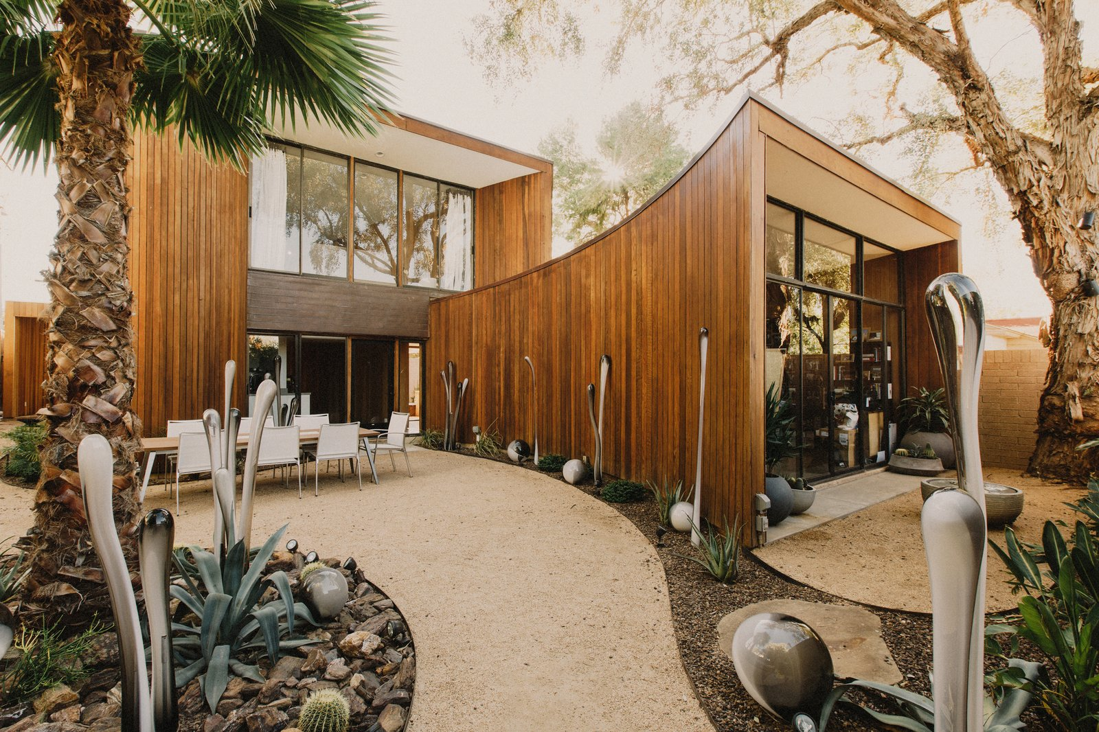 Custom whimsical glass sculptures created by Rainier Glass Studio and succulents highlight the courtyard of this curved house in central Phoenix