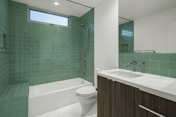 Modern home with bath room, undermount sink, porcelain tile floor, alcove tub, engineered quartz counter, open shower, ceiling lighting, two piece toilet, and glass tile wall. Main bathroom Photo 20 of Sol House