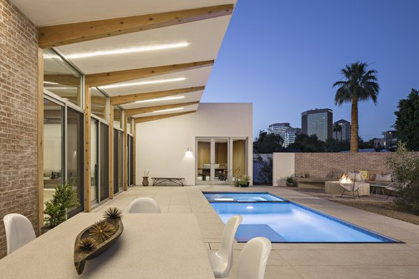 Modern home with outdoor, side yard, desert, small pool, pavers patio, porch, deck, and decomposed granite patio, porch, deck. The courtyard lit up at night with midtown Phoenix beyond. Photo 15 of Sol House