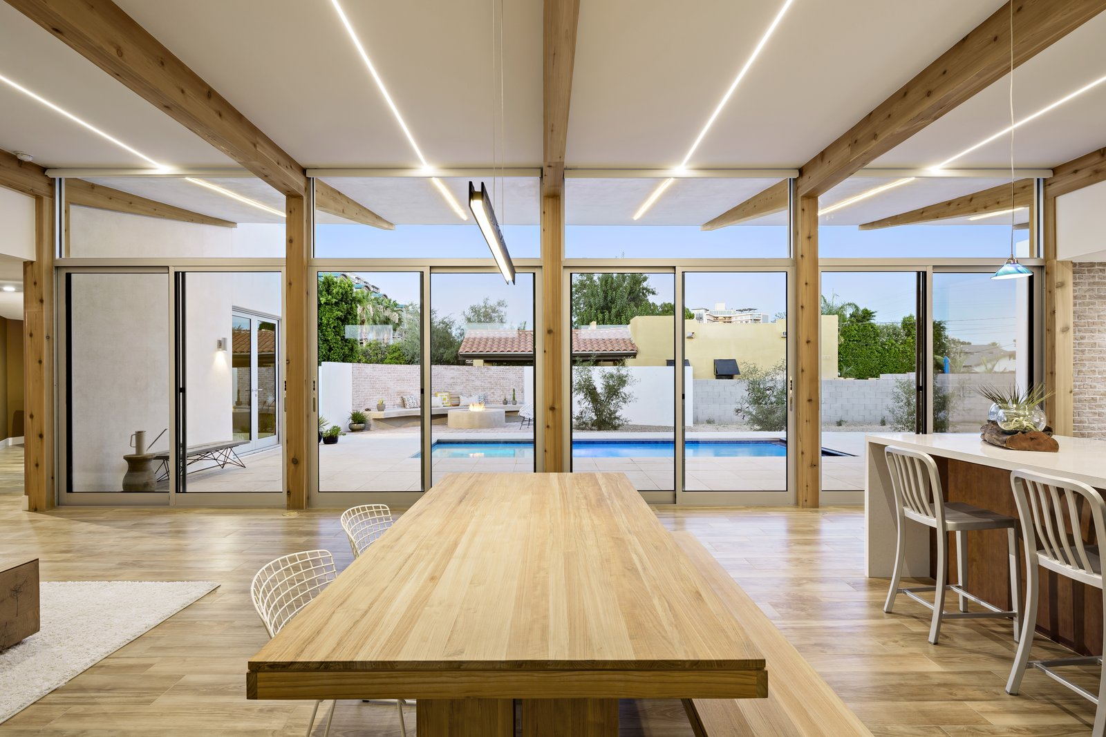 Integrated, dimmable LED lighting provides even light throughout the space and extends to the cantilevered patio outside. Tagged: Dining Room, Table, Bench, Chair, Ceiling Lighting, and Porcelain Tile Floor.  Sol House by The Ranch Mine