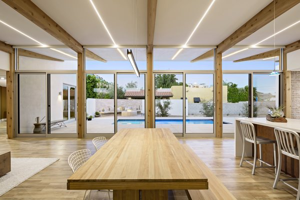 Modern home with dining room, table, bench, chair, ceiling lighting, and porcelain tile floor. Integrated, dimmable LED lighting provides even light throughout the space and extends to the cantilevered patio outside. Photo 12 of Sol House