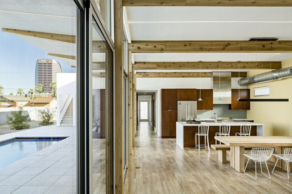 Modern home with dining room, ceiling lighting, table, bench, pendant lighting, and porcelain tile floor. The wood beams flow from inside to outside and angle up to capture a view of the tallest tower in the area. Photo 9 of Sol House