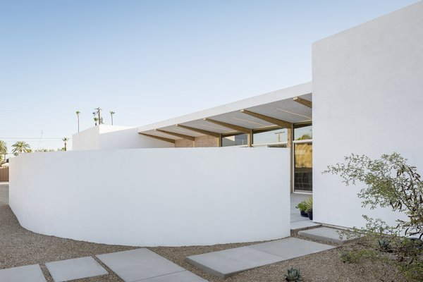 Modern home with outdoor, decomposed granite patio, porch, deck, desert, walkways, and side yard. A curved wall shields the courtyard beyond Photo 7 of Sol House