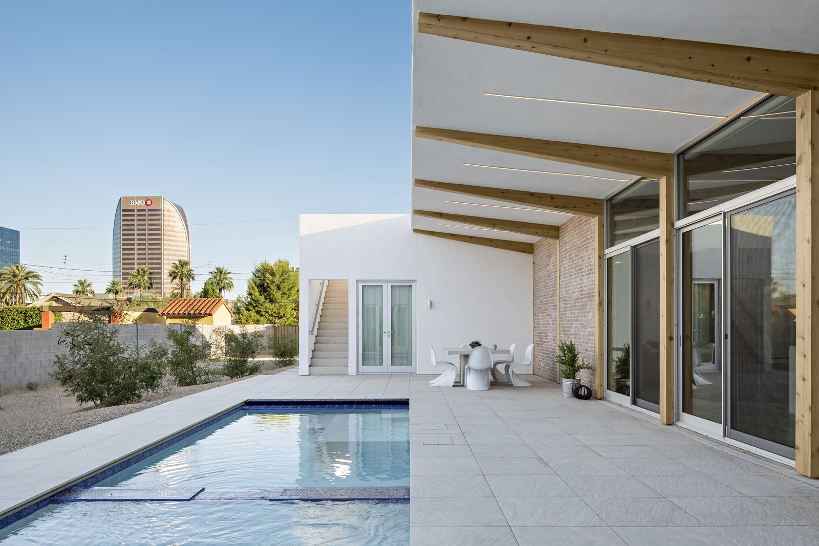 Cantilevered wood beams angle up towards the growing city skyline. On the left, a sloped area captures the monsoon rainfall and the Mulga Acacia trees will grow to the height of the home over time to provide more shade and privacy.