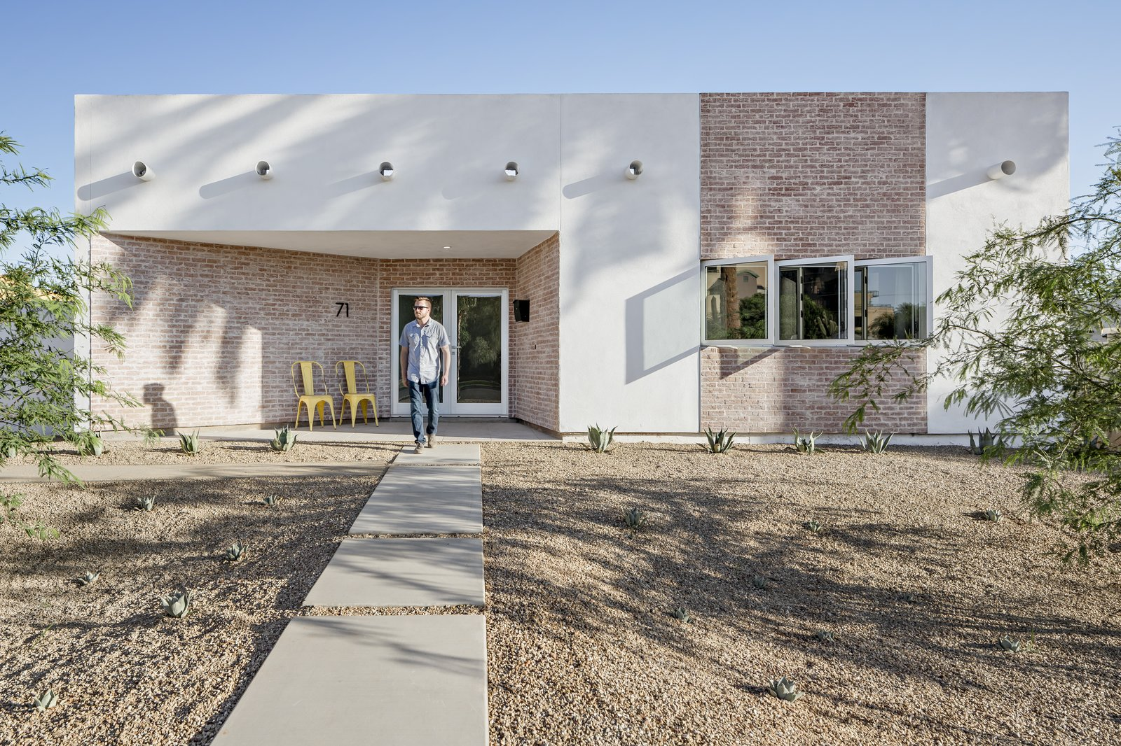 The front uses common materials to the neighborhood in a new modern way. A recessed front porch walls flare out as if to welcome the community Tagged: Outdoor, Front Yard, Shrubs, Desert, Small Patio, Porch, Deck, Decomposed Granite Patio, Porch, Deck, Pavers Patio, Porch, Deck, and Walkways.  Sol House by The Ranch Mine
