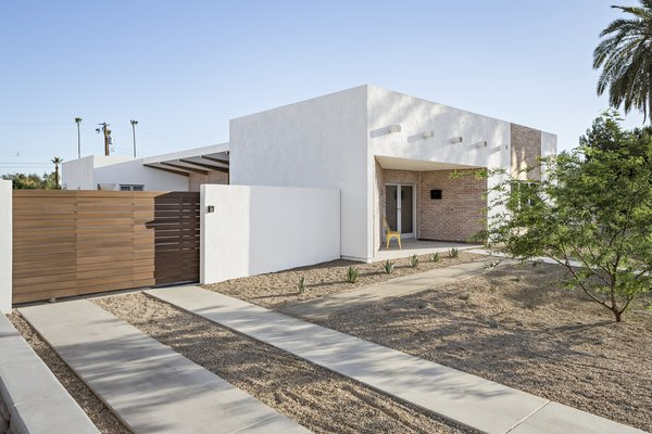 Modern home with outdoor, front yard, desert, trees, shrubs, pavers patio, porch, deck, and decomposed granite patio, porch, deck. Driveway lanes lead to a rolling gate for everyday parking. A 2 car garage is accessed of the alley in the rear. Photo 6 of Sol House
