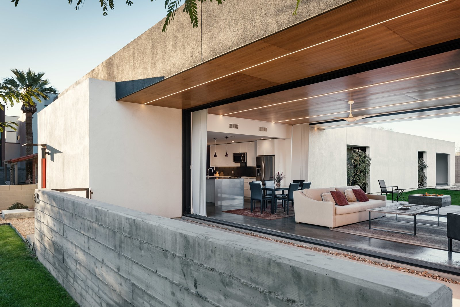 A board formed concrete wall creates a solid barrier off of the open living space to allow the homeowner to feel safe yet open to the community Tagged: Trees, Front Yard, Grass, Ceiling Lighting, Concrete Floor, Concrete Patio, Porch, Deck, and Outdoor.  Link House by The Ranch Mine
