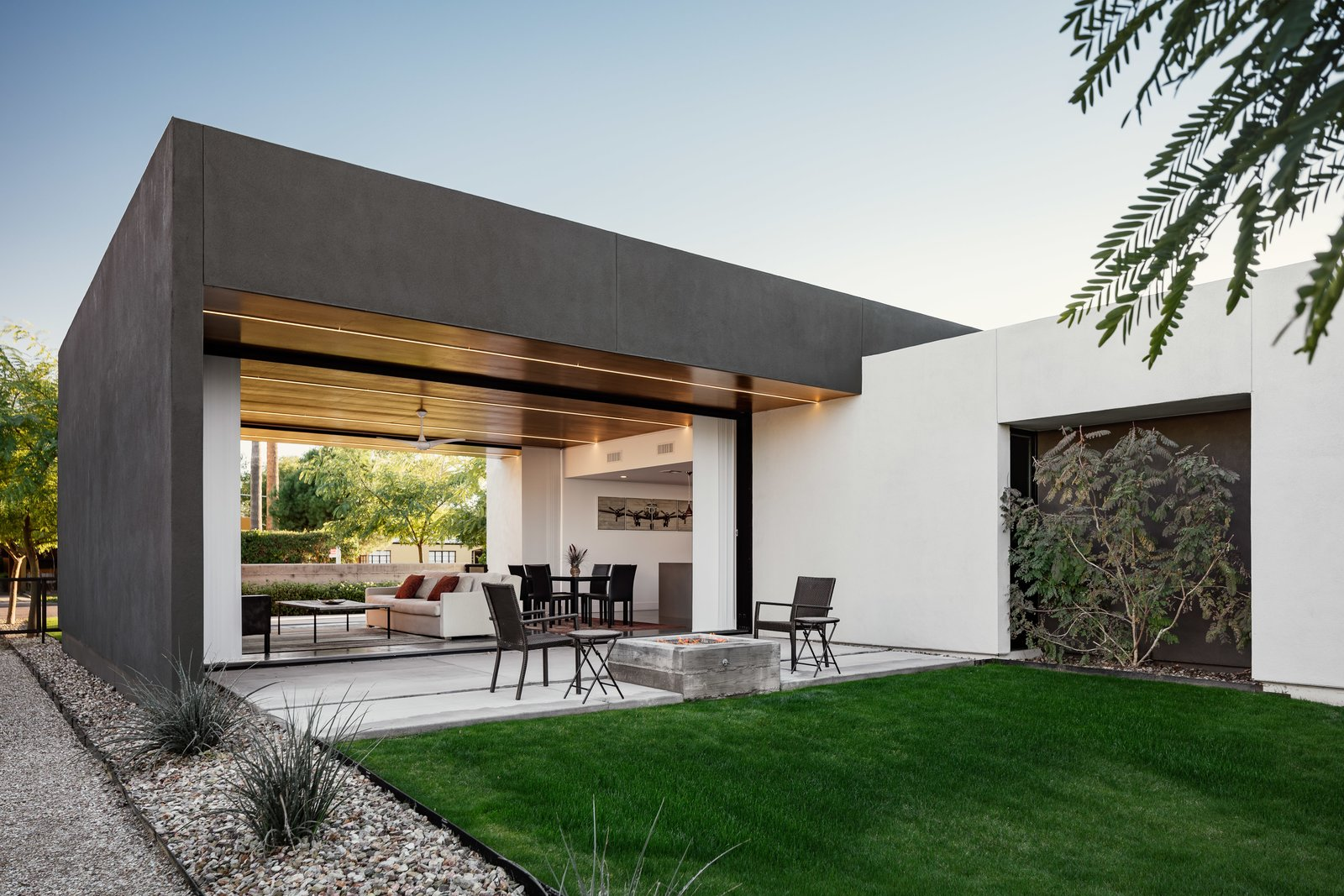 A board formed concrete fire pit draws you out to the back patio from the open living space Tagged: Concrete Patio, Porch, Deck, Front Yard, Trees, Ceiling Lighting, Concrete Floor, Back Yard, Grass, Exterior, and Stucco Siding Material.  Link House by The Ranch Mine