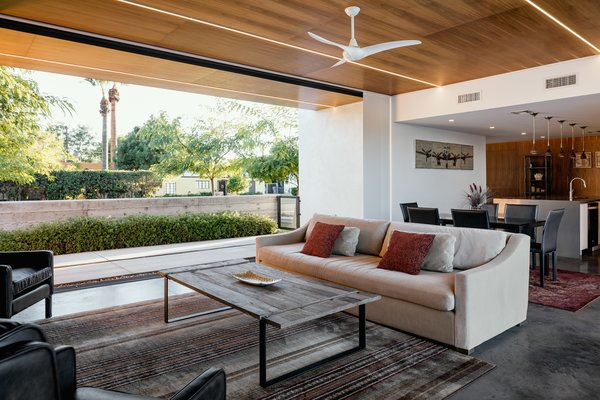 Modern home with concrete patio, porch, deck, shrubs, trees, living room, front yard, sofa, coffee tables, ceiling lighting, and concrete floor. The walnut clad ceiling extends over the kitchen to the entry Photo 3 of Link House