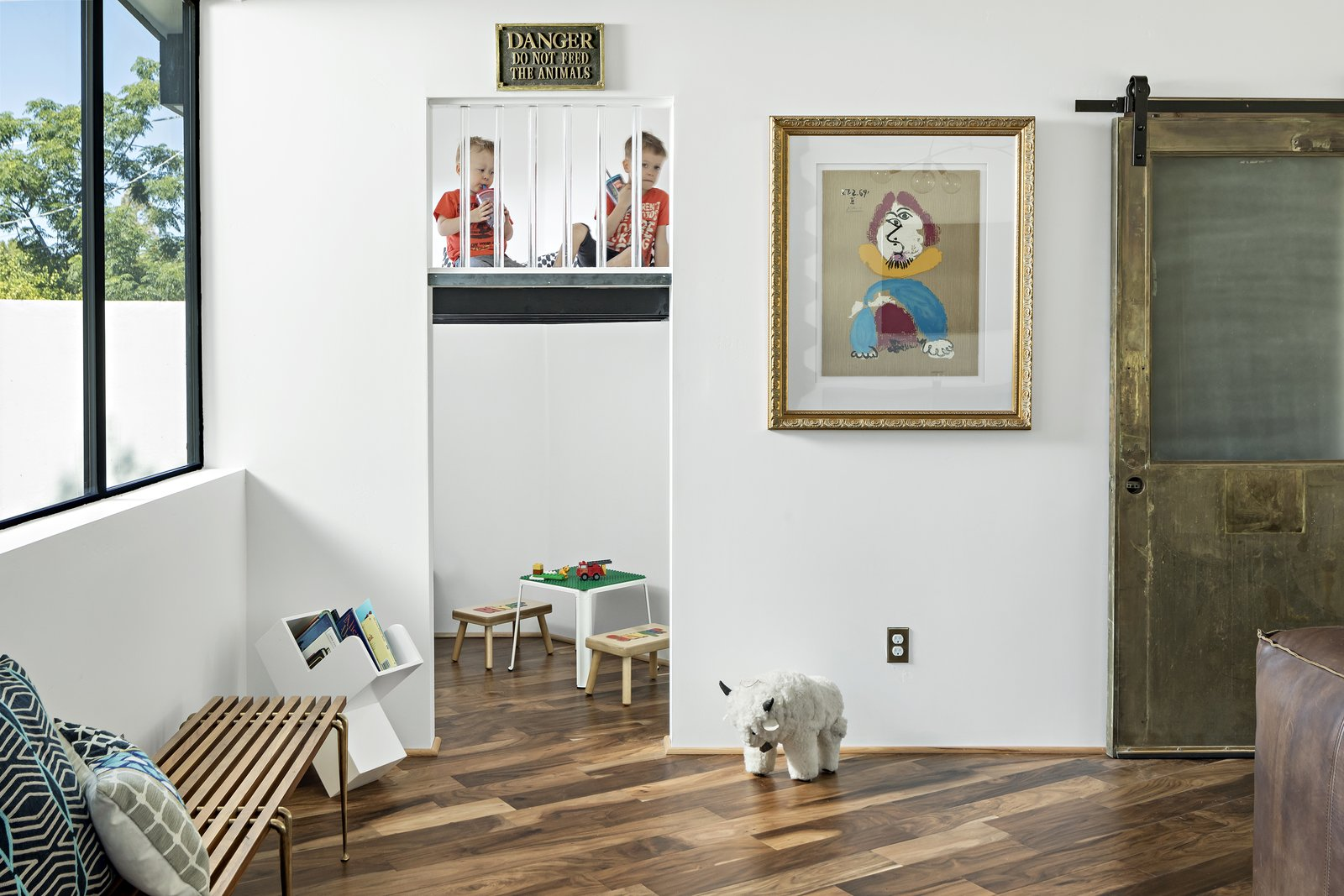 Kid's nook features a hidden brass ladder up to a lucite enclosed play space. Reclaimed brass door hides toy storage