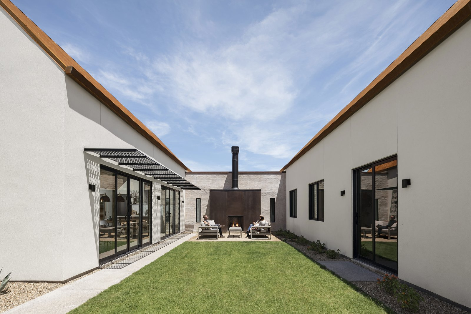 Central Courtyard anchored by a fireplace with the vaulted great room on the left, and bedroom wing on the right.