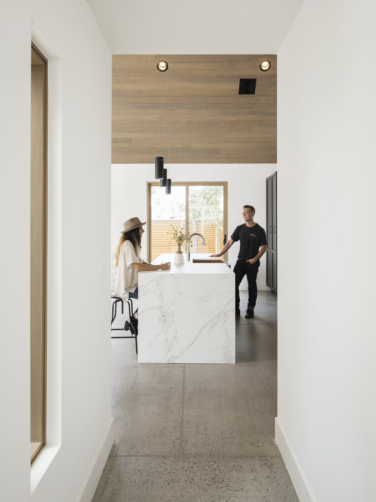 Waterfall edge on the Dekton counter. The floors are exposed aggregate concrete Tagged: Kitchen, Engineered Quartz Counter, and Pendant Lighting. Canal House by The Ranch Mine