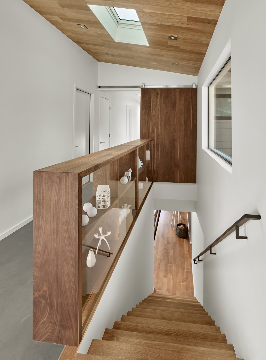 The sliding door and open shelves are by Matt Eastvold and are made of solid walnut. The ceiling features prefinished white oak and the floor is a thin cementitous product Ardex. this space serves as the main core of the home and connection between the living areas, entry, and bedroom areas. Trestle Glen Modern by Knock Architecture + Design