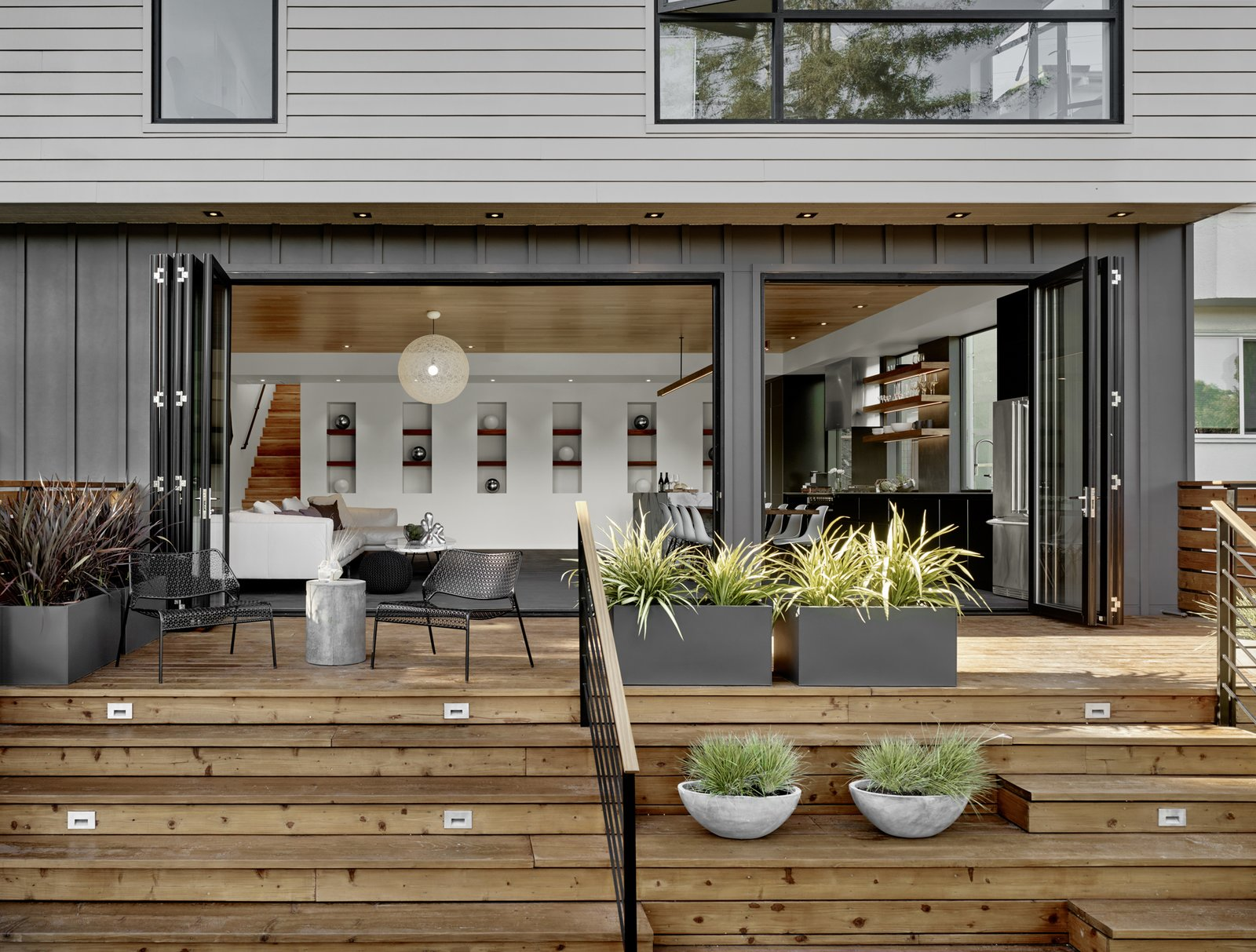 The back of the house features a combination of Hardi-Panel lap siding and board and batten, which are in a series of greys softened by the redwood deck and plantings. Tagged: Outdoor.  Trestle Glen Modern by Knock Architecture + Design