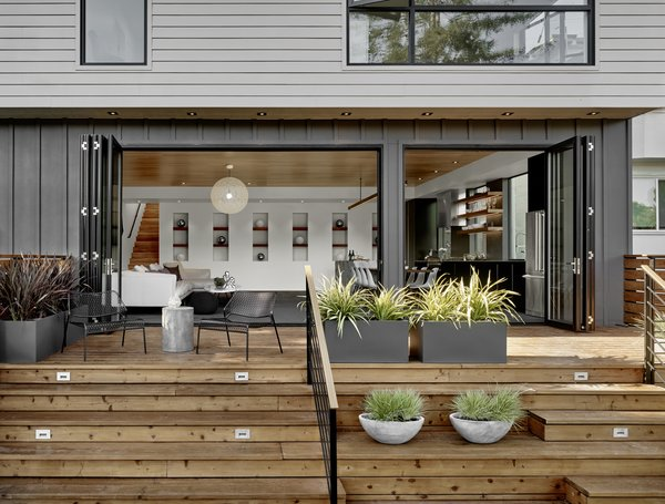 The back of the house features a combination of Hardi-Panel lap siding and board and batten, which are in a series of greys softened by the redwood deck and plantings. Photo 7 of Trestle Glen Modern modern home