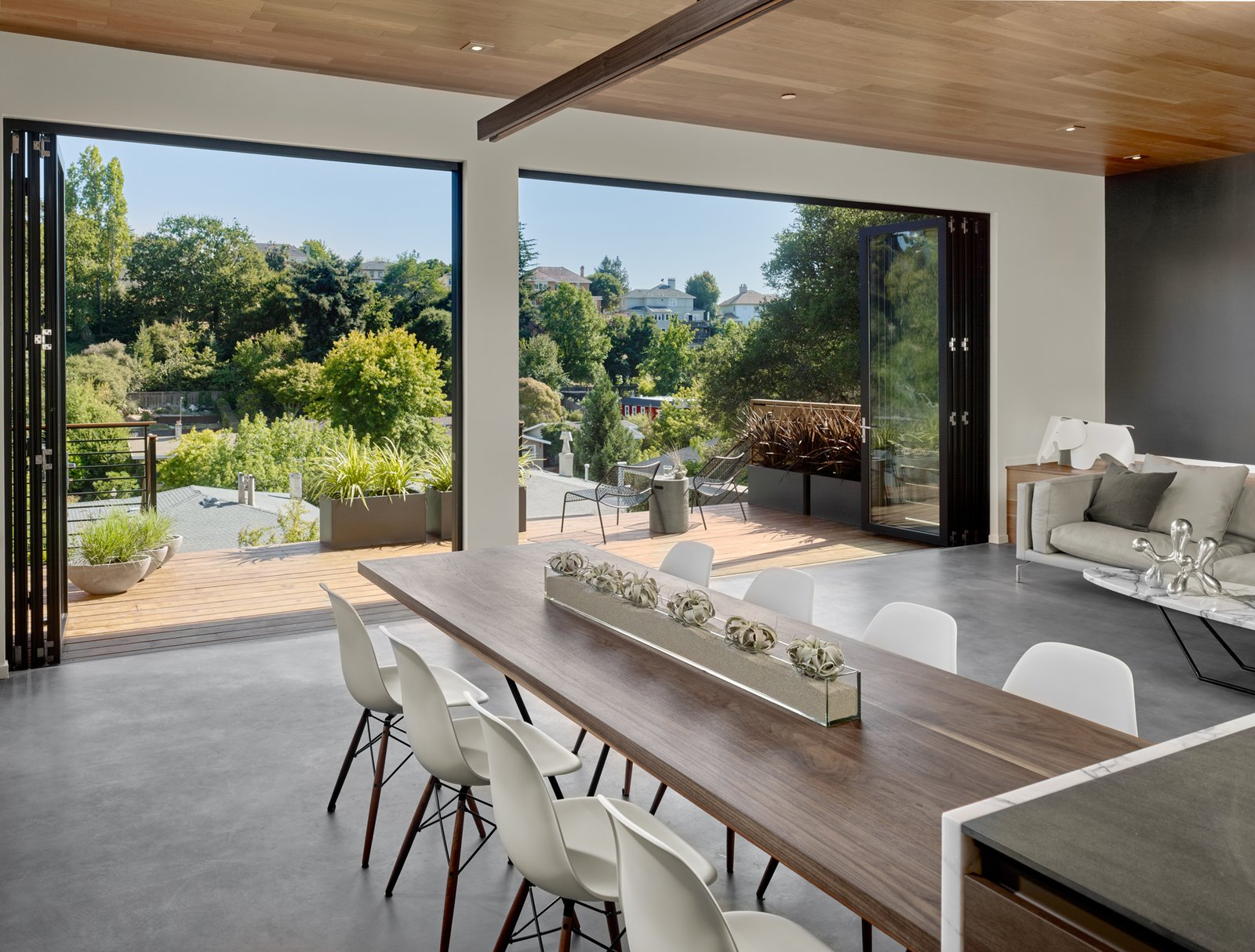 The foldings doors are by La Cantina, which expand to a redwood deck and the view across the valley. Tagged: Dining Room, Table, and Chair.  Trestle Glen Modern by Knock Architecture + Design
