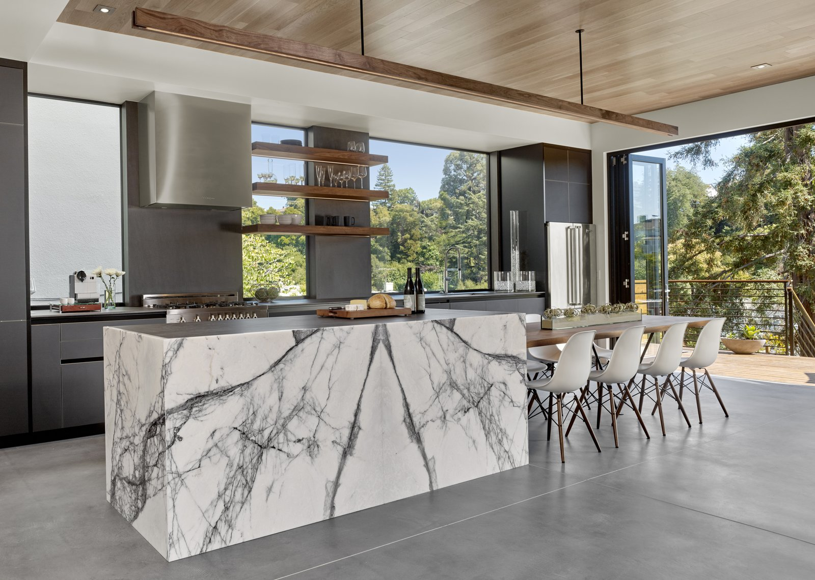 The cabinets are black matte glass by Leicht. The floating walnut table, shelves and light are by Matt Eastvold. Tagged: Kitchen, Range Hood, Refrigerator, and Marble Counter.  Trestle Glen Modern by Knock Architecture + Design