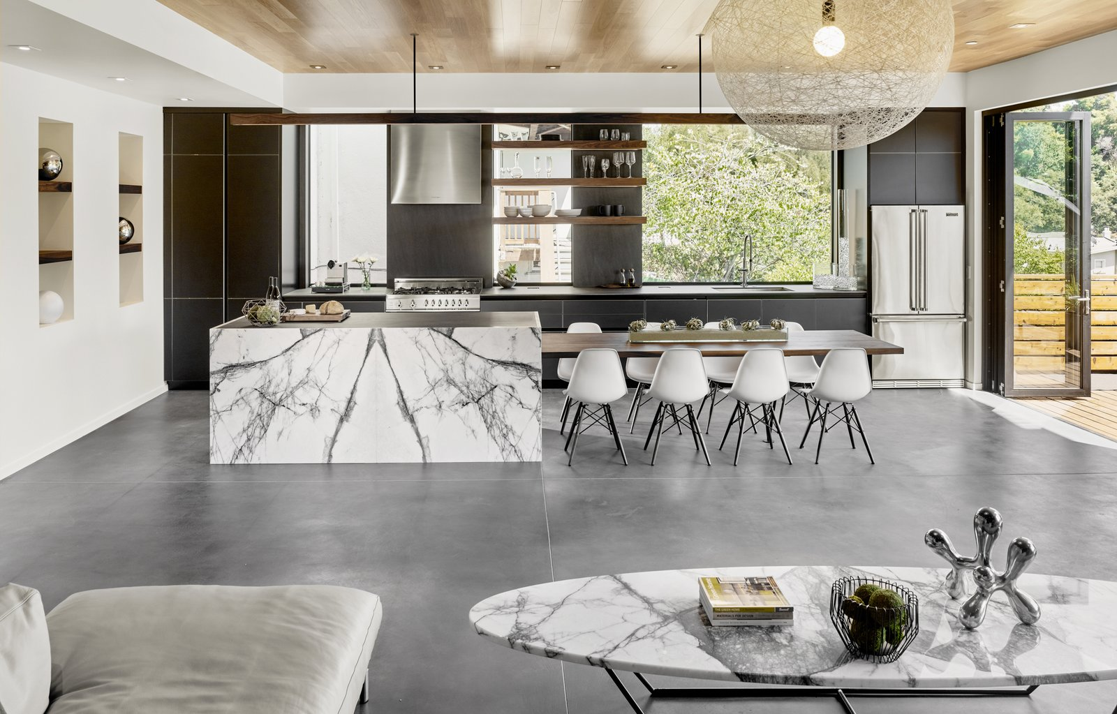 The floors have hydronic heating embedded in a matte finished concrete. The stone slab is Calacatta Viola. The table is custom designed by the architect and fabricated by Gerardo Villa.
