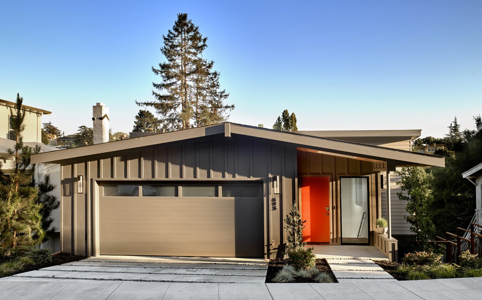 Pervious large concrete pavers are used for the garage drive and entry. The entry porch is setback and features a large skylight that allows light to pass through to the floors below   Trestle Glen Modern by Knock Architecture + Design