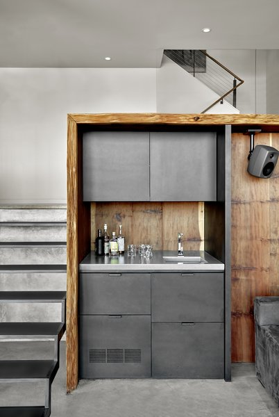 The wetbar area features custom steel cabinets by Metropolis Metalworks, and the burled redwood paneling and slab, sourced via Aborica and fabricated by Artistic Veneers.