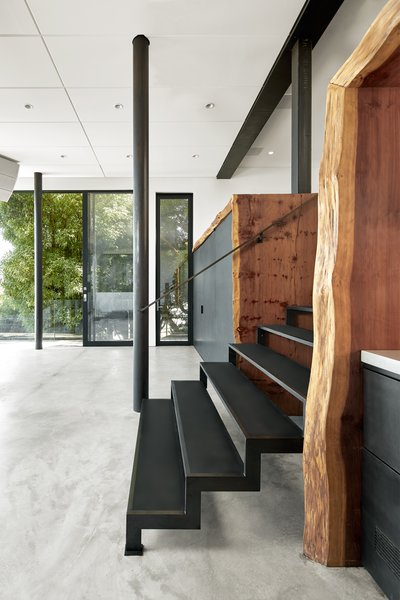 The burled redwood slab from Aborica serves as a dramatic portal as you descend into the lower zone of the Escape Pad. The custom partition housing the tub and powder room area lie beyond. The custom metal works was by Metropolis Metalworks.