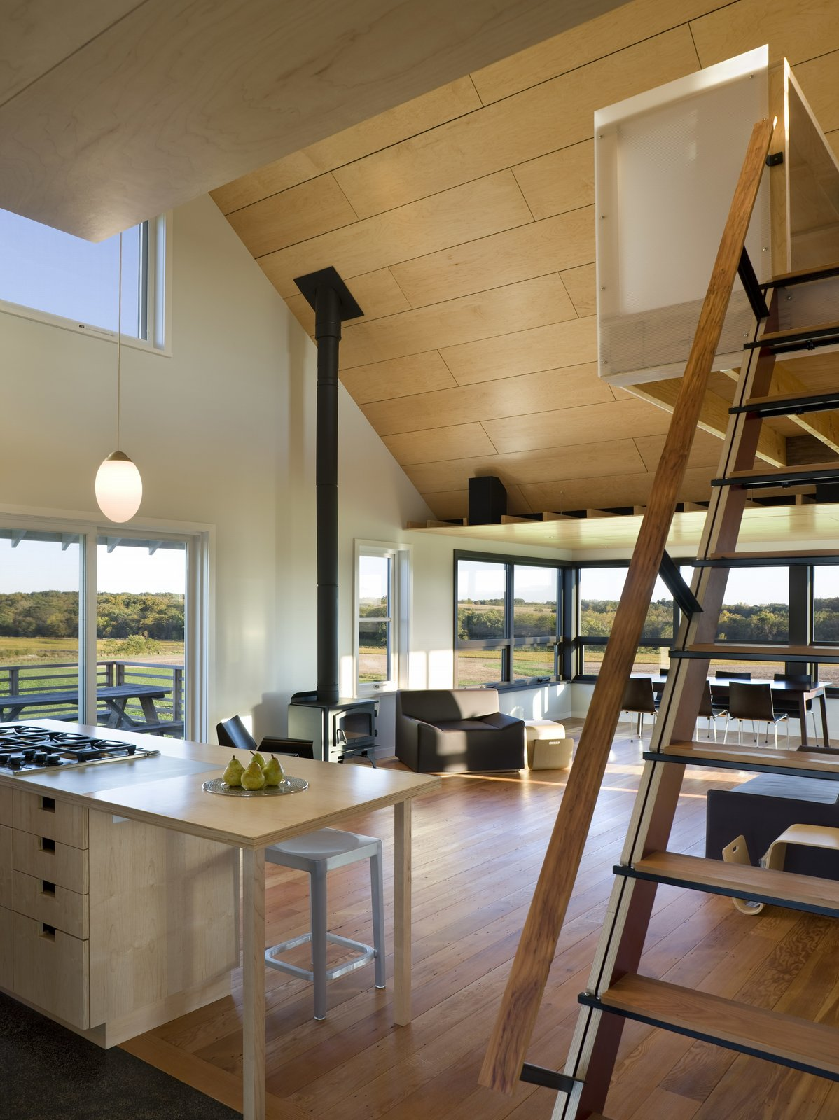 Sliding fabric panels allow the enclosed porch to be used for dining or overflow sleeping. A loft overlooking the main living space and views of the farm serves as office space.