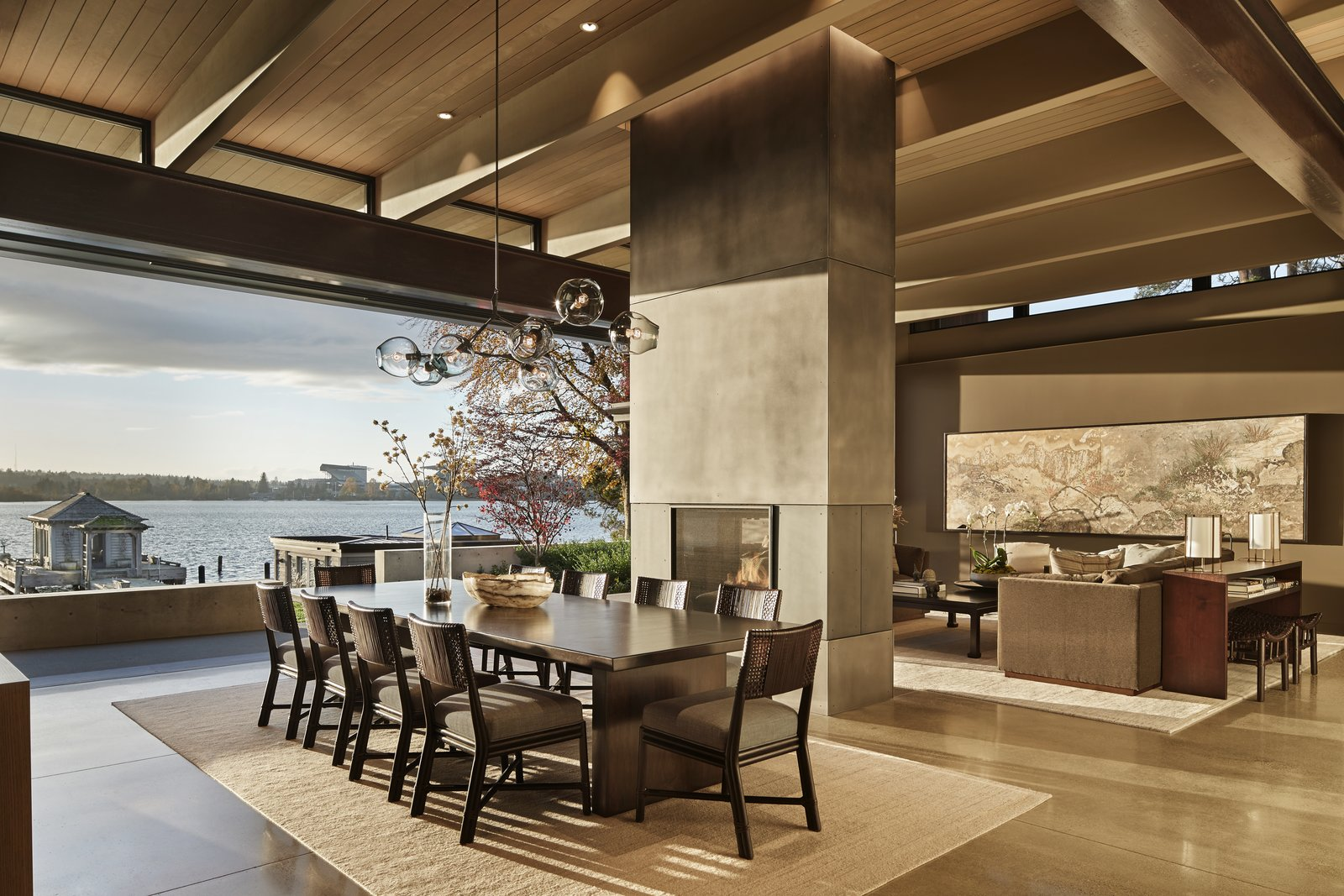 Great Room with steel-clad fireplace, concrete floors and wood beams Tagged: Living Room, End Tables, Sofa, Ceiling Lighting, Concrete Floor, Two-Sided Fireplace, Chair, and Console Tables.  Best Photos from Union Bay Residence