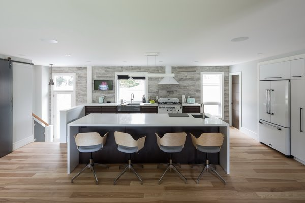 The kitchen which is central to family life, commands the area opposite the entry. Photo 15 of Burlington Residence modern home