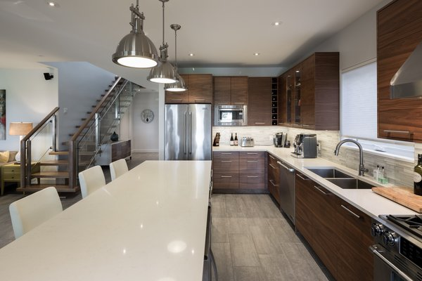 The space is anchored with a custom designed kitchen and island. Photo 13 of Turkey Point Beach House modern home