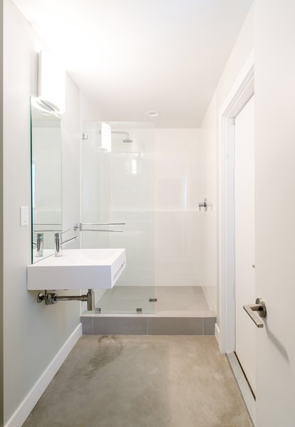 A new compact white bathroom with concrete flooring and open shower is accessed from a new guest bedroom behind the kitchen, as well as from the rear yard.