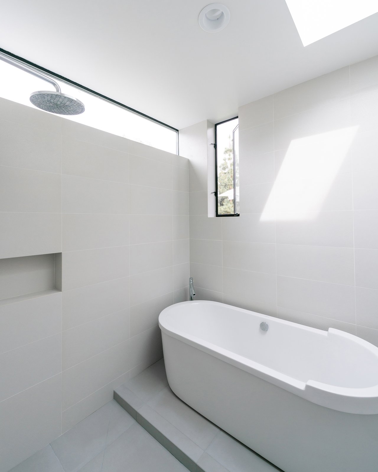 At the rear of the home, the master suite addition adds a full wet room with skylight, a rain shower and freestanding tub.