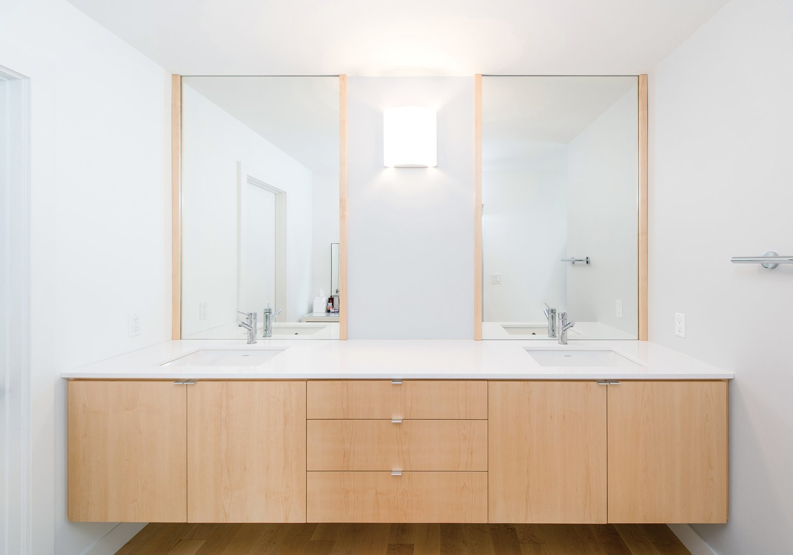 Floating maple cabinetry at the master bath vanity provides for material continuity throughout the home's minimalist interior. Tagged: Bath Room, Engineered Quartz Counter, Wall Lighting, Undermount Sink, and Light Hardwood Floor.  Villa Park Modern by MYD studio, inc.