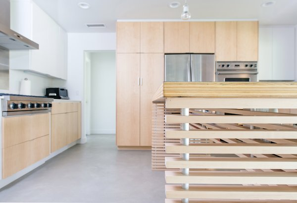 The oversized kitchen island utilizes a structure of aluminum spacers at maple slats to support the plywood and stainless steel top.