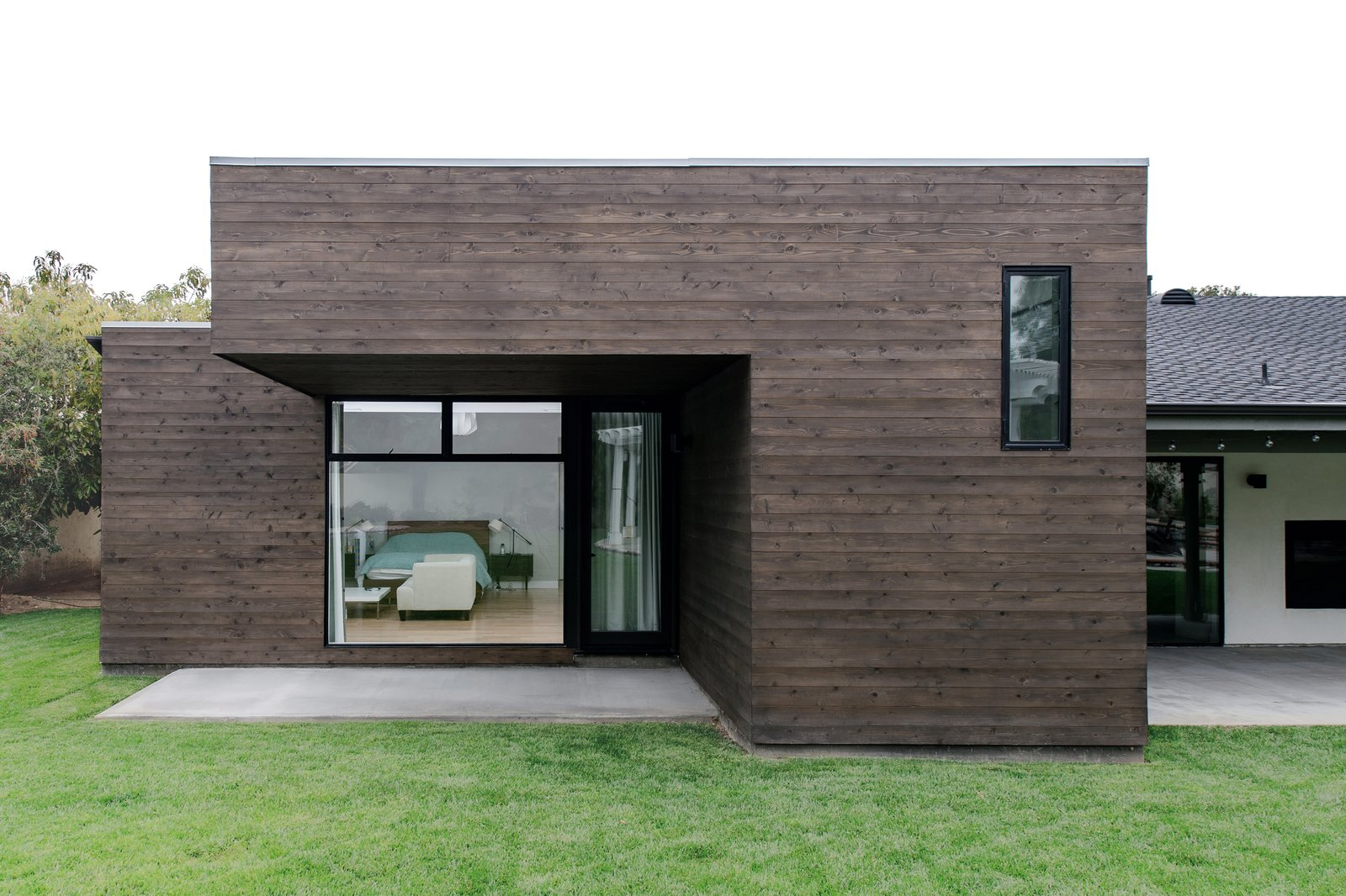 The dark stained cedar-clad cantilever with flat roof juxtaposes the existing traditional details and massing at the rear. Villa Park Modern by MYD studio, inc.