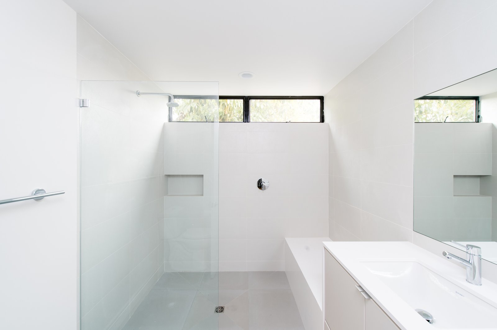 A minimalist secondary bath features a quartz waterfall bench and oversized custom shower. Tagged: Bath Room, Engineered Quartz Counter, Porcelain Tile Floor, Undermount Sink, Open Shower, Ceiling Lighting, and Ceramic Tile Wall.  Villa Park Modern by MYD studio, inc.