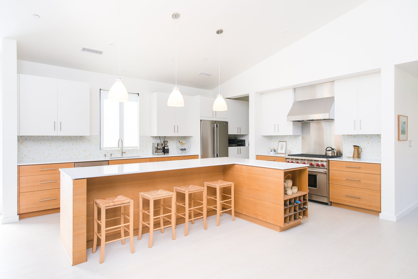 The l-shaped island at the open kitchen encourages gathering while cooking.