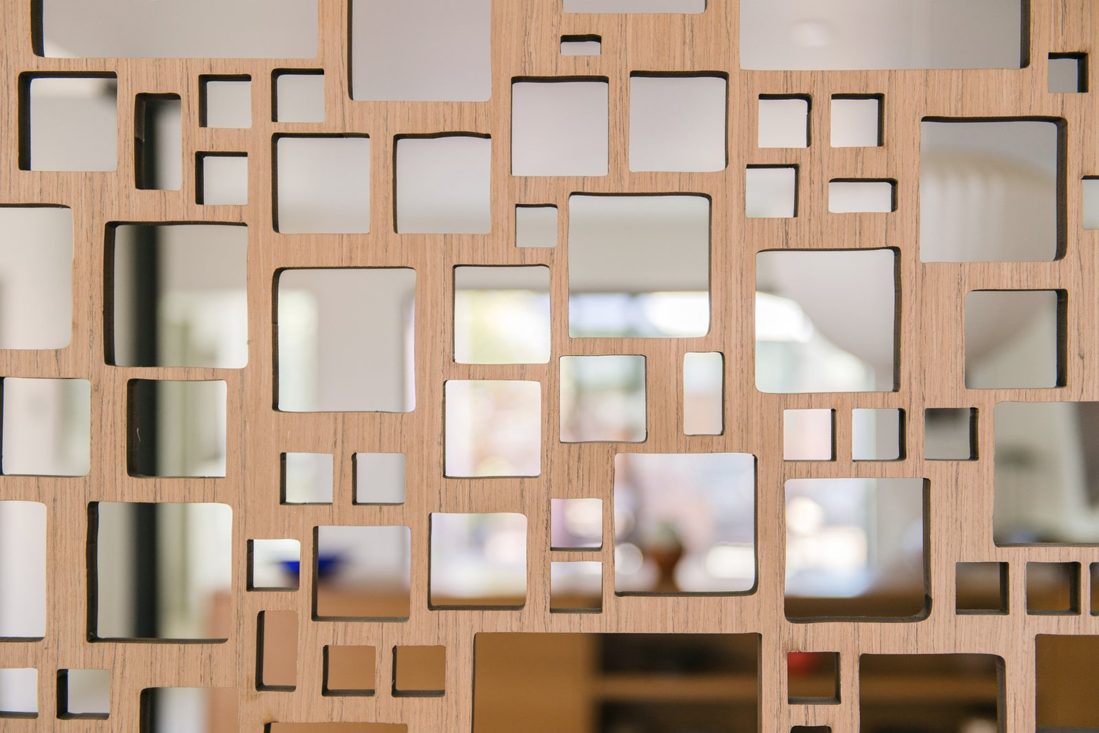 A mid-century inspired wood screen adds a playful geometry and element of privacy at the entry.
