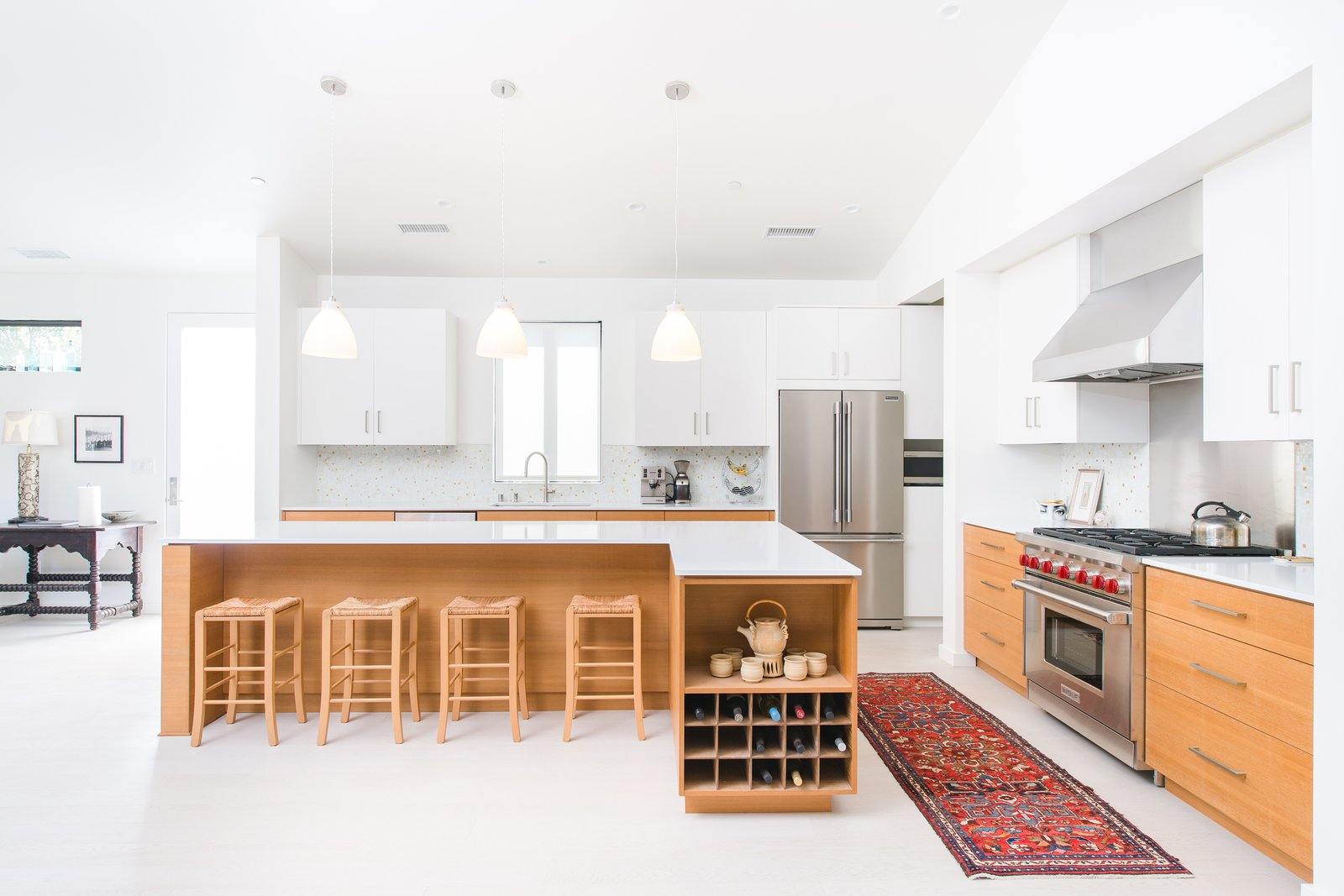 Light wood flooring complements the warmth of the custom teak cabinetry and white quartz kitchen.