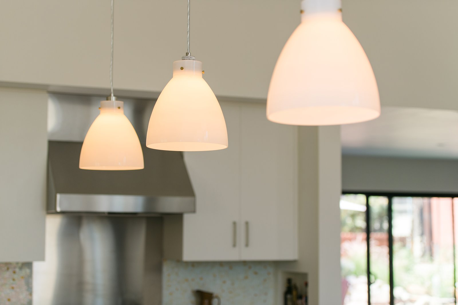 Minimal pendants add warm, intimate lighting at the oversized kitchen island.