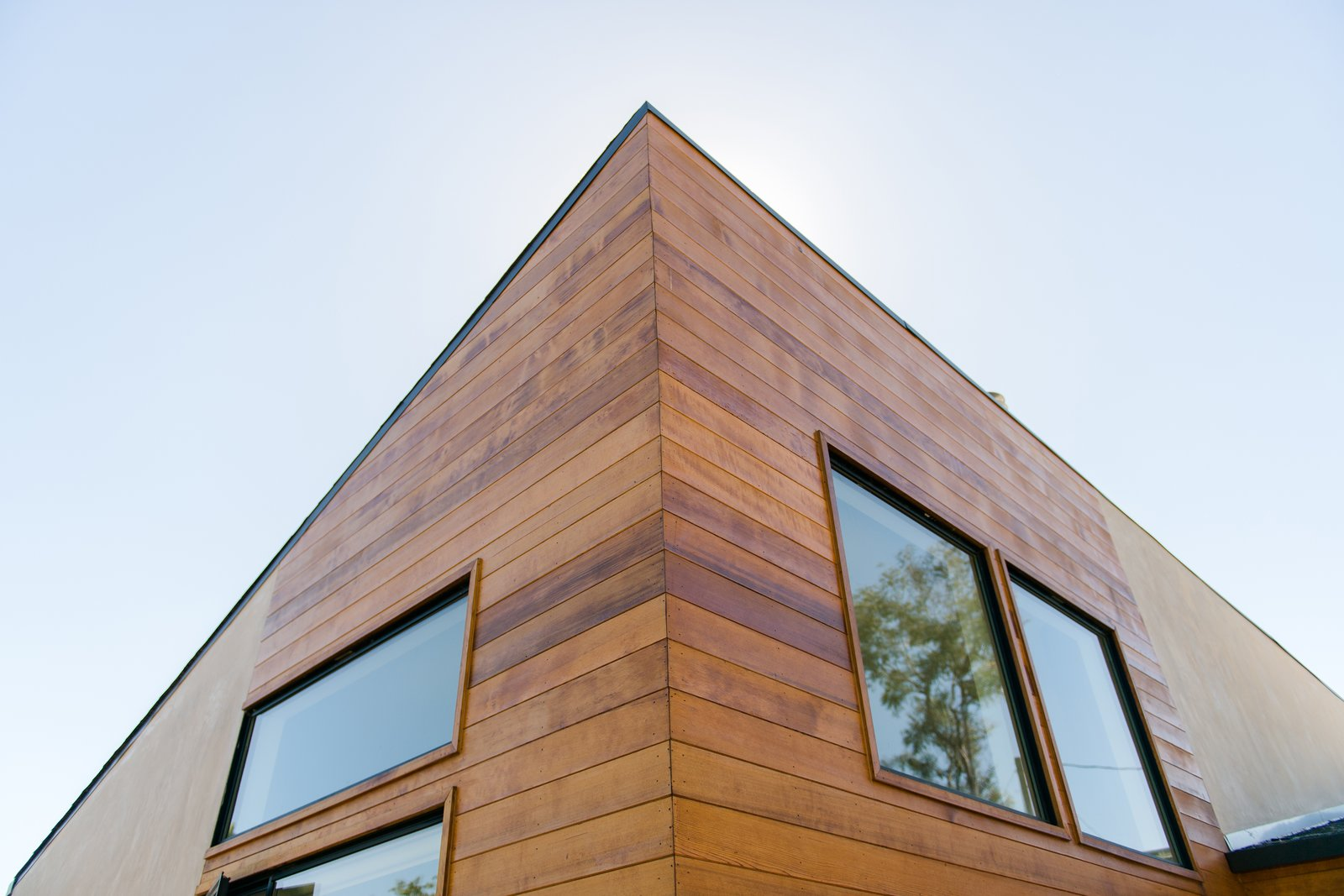 Exterior cedar siding adds asymmetrical interest at the new angled roof at the front addition. Tagged: Exterior, House, Ranch Building Type, Wood Siding Material, and Stucco Siding Material.  A California Ranch Home, Reimagined by MYD studio, inc.