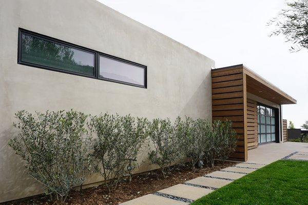 Modern home with exterior, walkways, swing door type, hardscapes, horizontal fence, wood fence, concrete patio, porch, deck, attached garage, stone patio, porch, deck, gardens, decomposed granite patio, porch, deck, and outdoor. A linear metal window and increased roof height at the stucco parapet adds visual interest and subtle movement at the home's exterior massing. Photo 5 of Laguna Niguel Mid-Century
