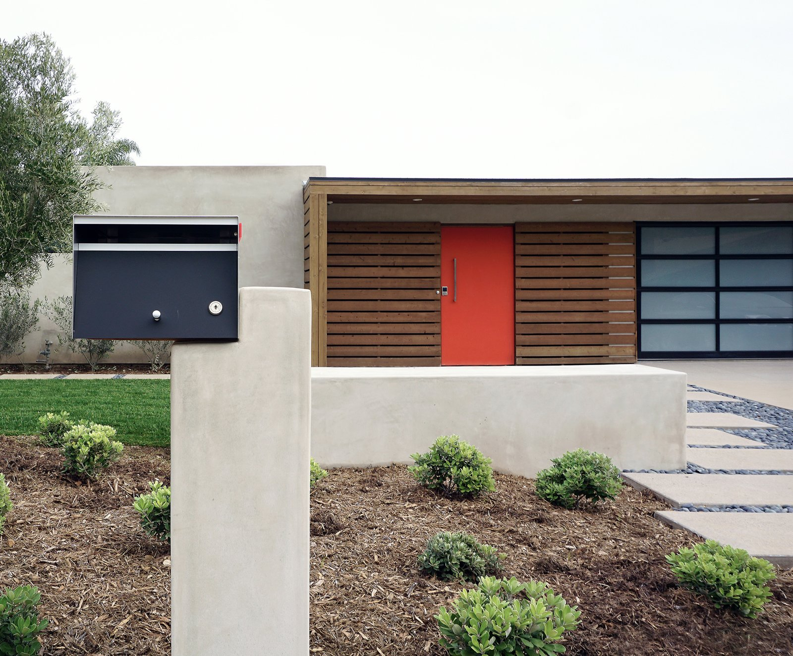An asymmetrical mailbox incorporates mid-century geometry and new building materials into the front approach. Tagged: Swing Door Type, Wood Fences, Wall, Hardscapes, Walkways, Exterior, Horizontal Fences, Wall, Concrete Patio, Porch, Deck, Attached Garage, Stone Patio, Porch, Deck, Decomposed Granite Patio, Porch, Deck, Gardens, Shrubs, Grass, Front Yard, Small Patio, Porch, Deck, and Outdoor.  Photo 3 of 6 in 8 Best Modern Mailboxes to Buy from Laguna Niguel Mid-Century
