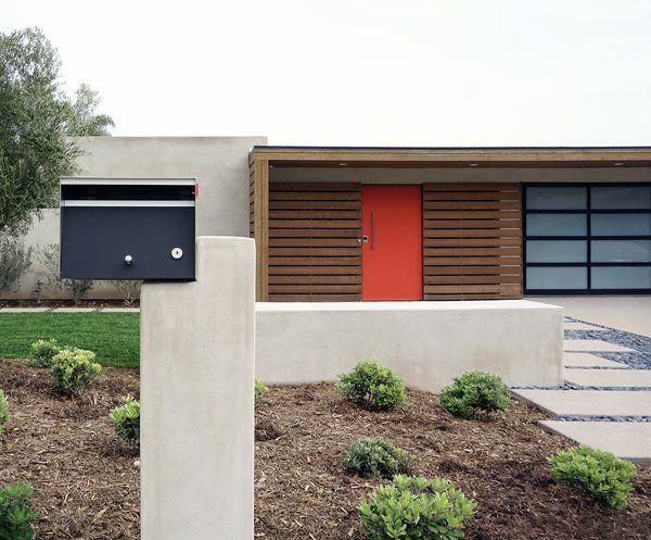 An asymmetrical mailbox incorporates mid-century geometry and new building materials into the front approach.