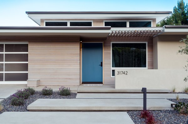 Modern home with outdoor, shrubs, hardscapes, walkways, concrete patio, porch, deck, small patio, porch, deck, and post lighting. blue door, staggered concrete and light-stained cedar at mid-century entry Photo 10 of Niguel West Mid-century Modern
