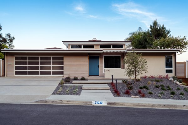 Modern home with outdoor, front yard, walkways, desert, hardscapes, trees, small patio, porch, deck, shrubs, concrete patio, porch, deck, horizontal fence, post lighting, and landscape lighting. coastal midcentury modern // entry + drought-tolerant landscaping Photo  of Niguel West Mid-century Modern