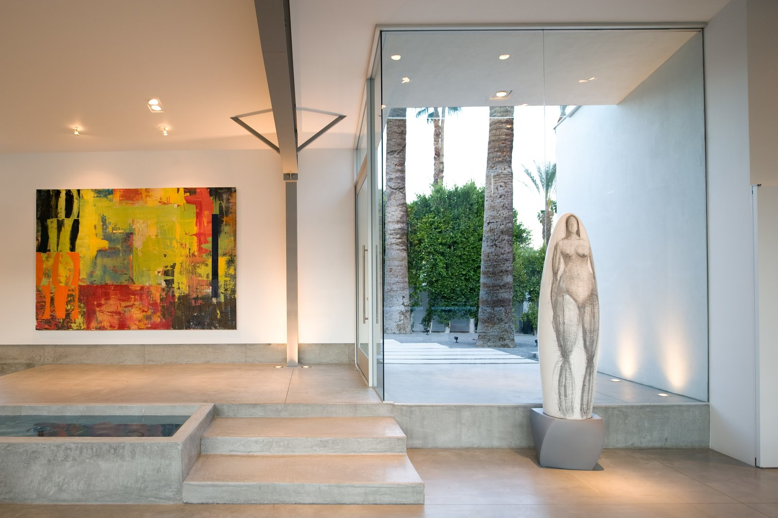 The front entrance opens into the great room next to a linear pond. The home becomes a perfect showcase for the owner's artwork collection.  Tagged: Living Room, Ceiling Lighting, Floor Lighting, and Concrete Floor.  Desert Canopy House by Sander Architects