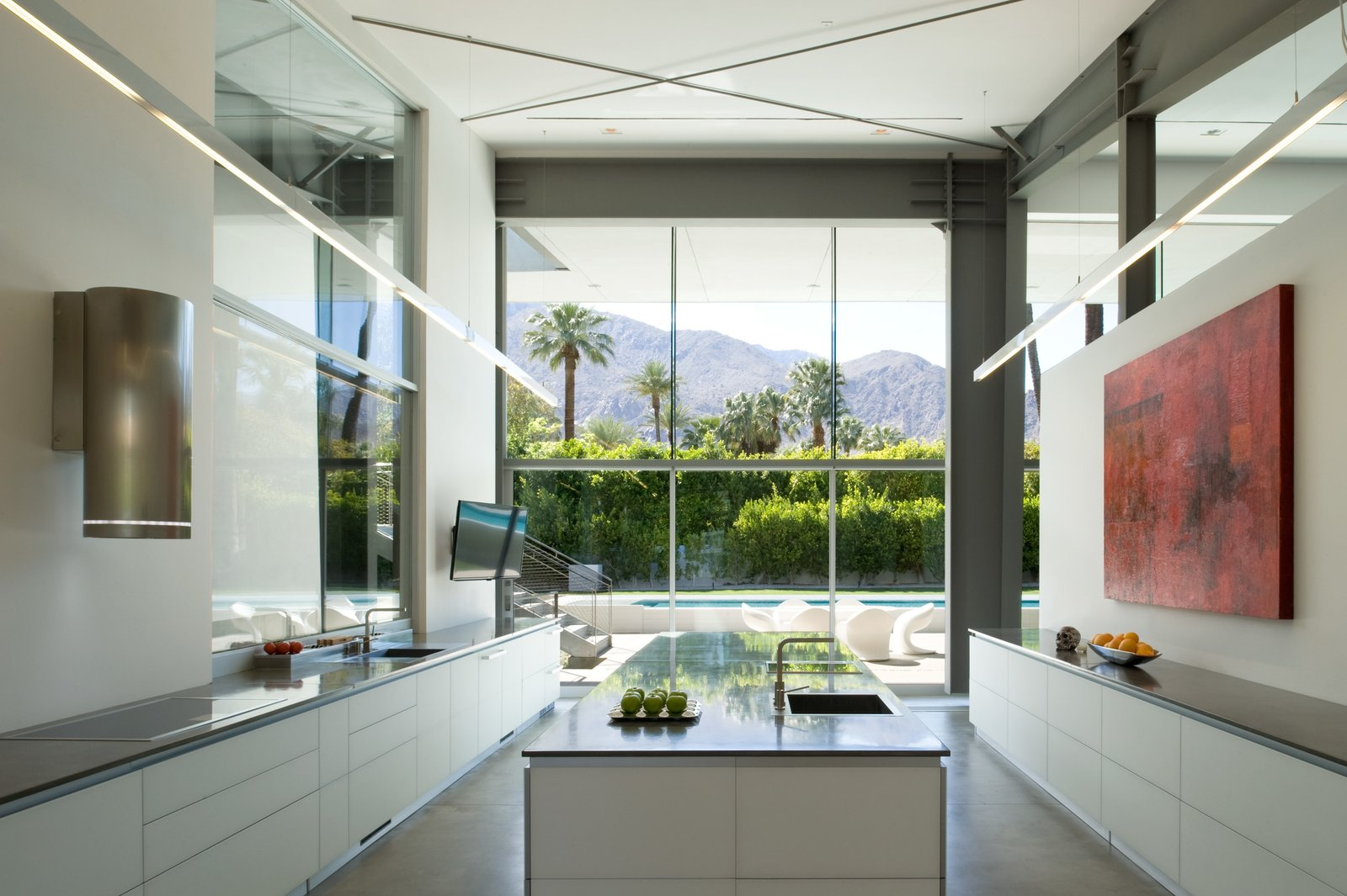 The glass wall on one end of the kitchen frames the mountain views. The cabinetry, all glass-fronted lowers,  with a convection stove and cylindrical vent make this room about the view and the art.