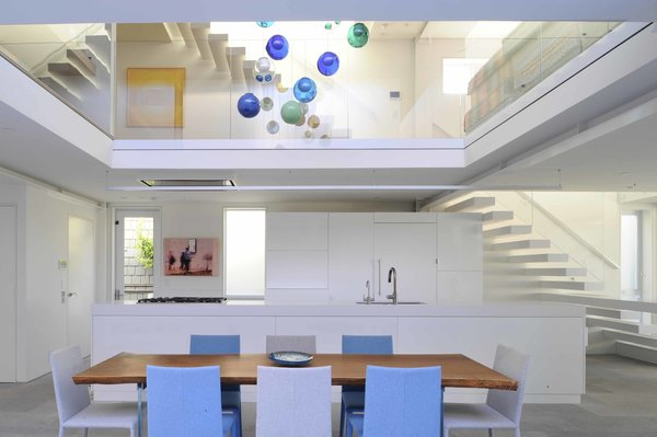 The all-white kitchen is open to the upper level. One tread of the stairs extends out to become a countertop and the live-edge dining room table is surrounded by blue and grey chairs that are part of a palette inspired by the beach setting.