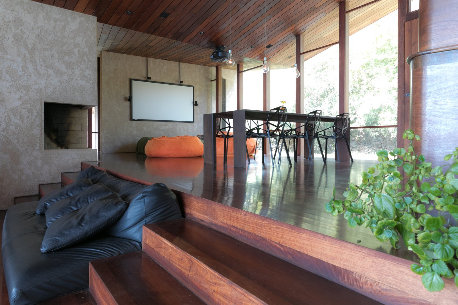 Tagged: Living Room, Sofa, Dark Hardwood Floor, Bench, and Corner Fireplace.  The Clifftop House by Modern on Maui - Liam Ball